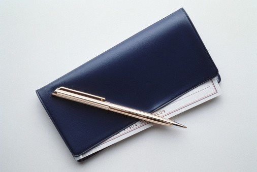 Black checkbook with check and pen.