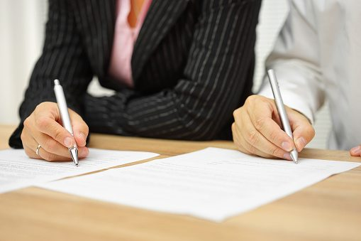 Man and woman signing an agreement