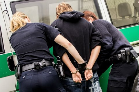 Two police arresting young man