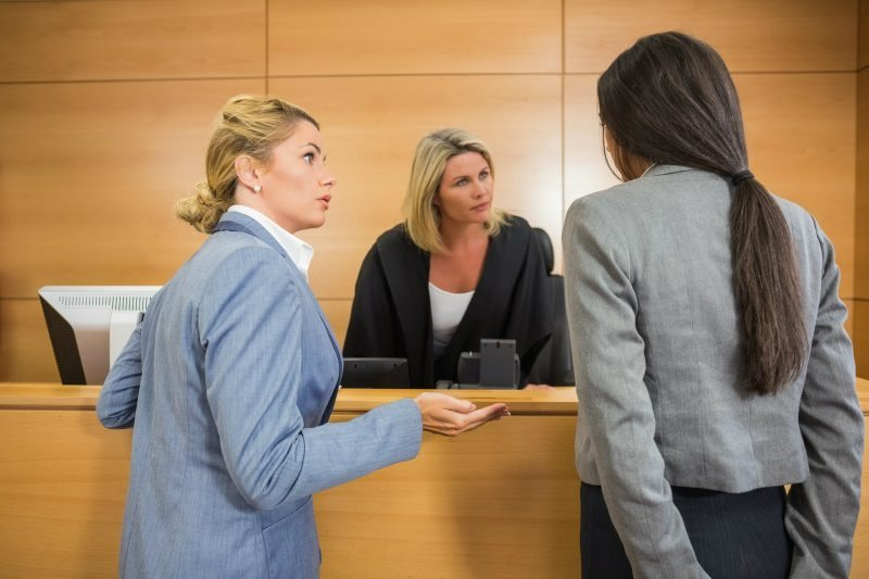 Woman and lawyer standing in front of judge